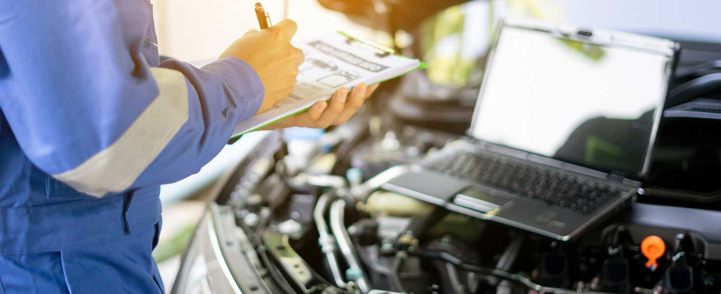 auto mechanic man or Smith writing to the clipboard at warehouse workshop, technician doing the checklist for repairs engine a car in the garage with laptop