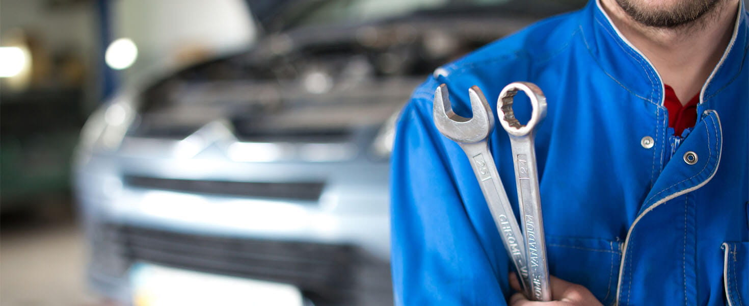 Auto mechanic holds wrench in hand at auto repair shop